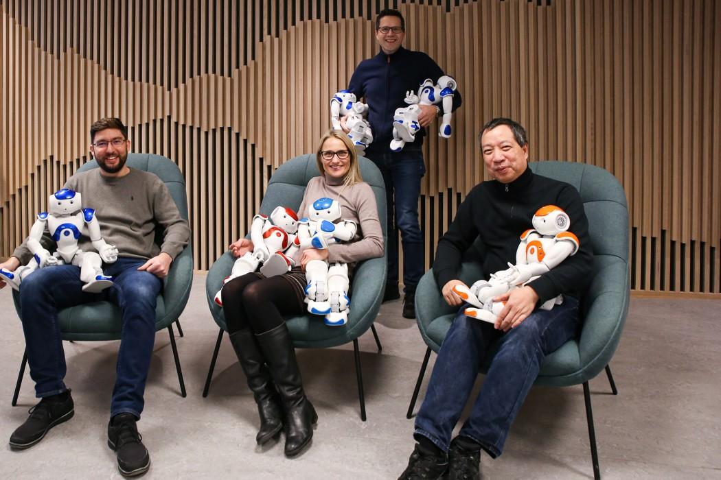 Fire forskere sitter med hver sin robot i fanget