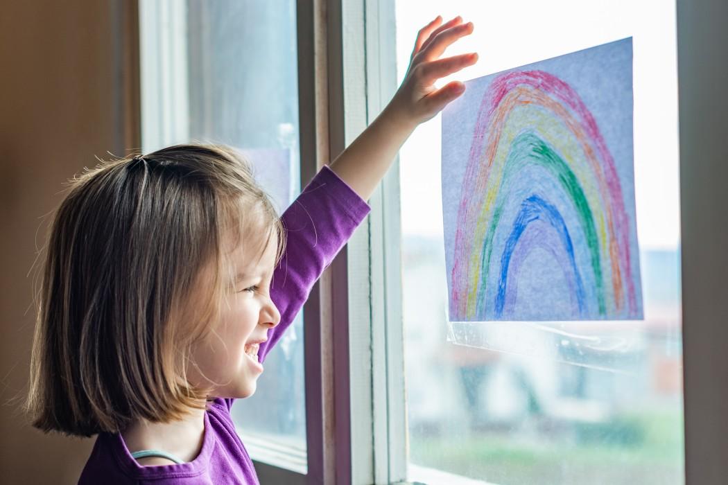Jente som ser på tegning av regnbue