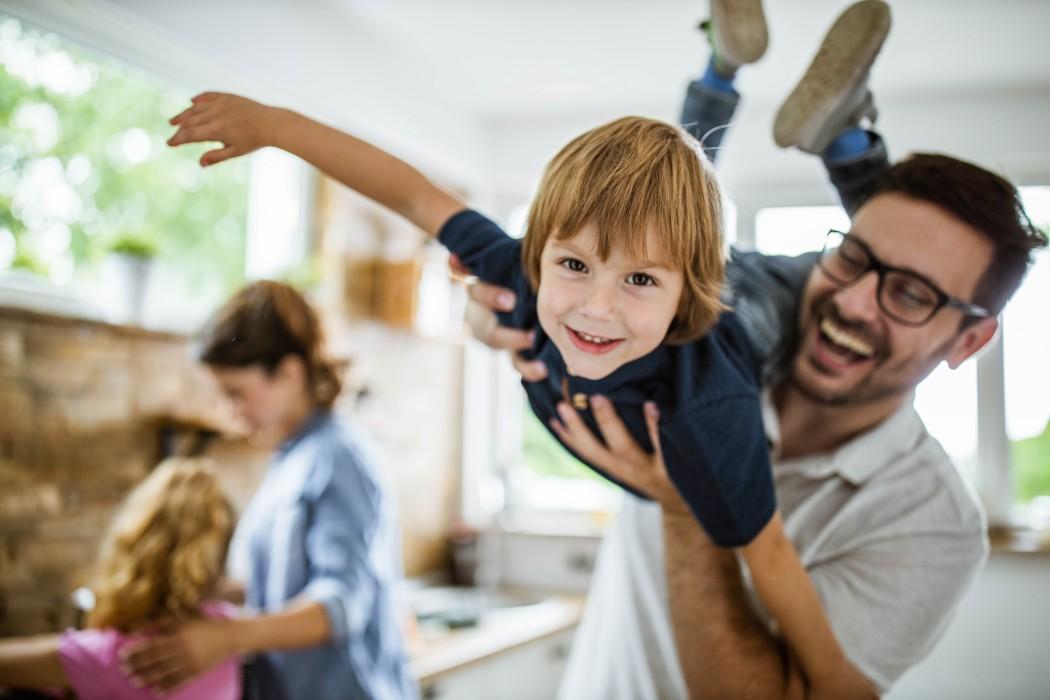 Mann løfter gutt opp på skuldra så han kan fly. Barn leker i bakgrunnen.