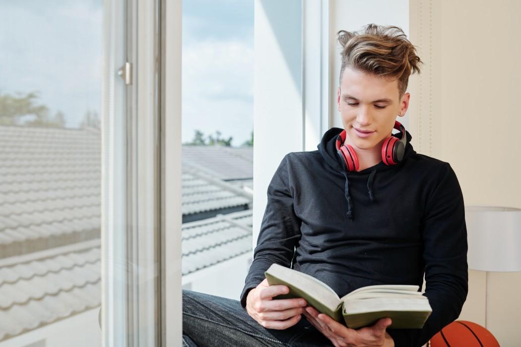 tenåringsgutt leser i vinduskarm