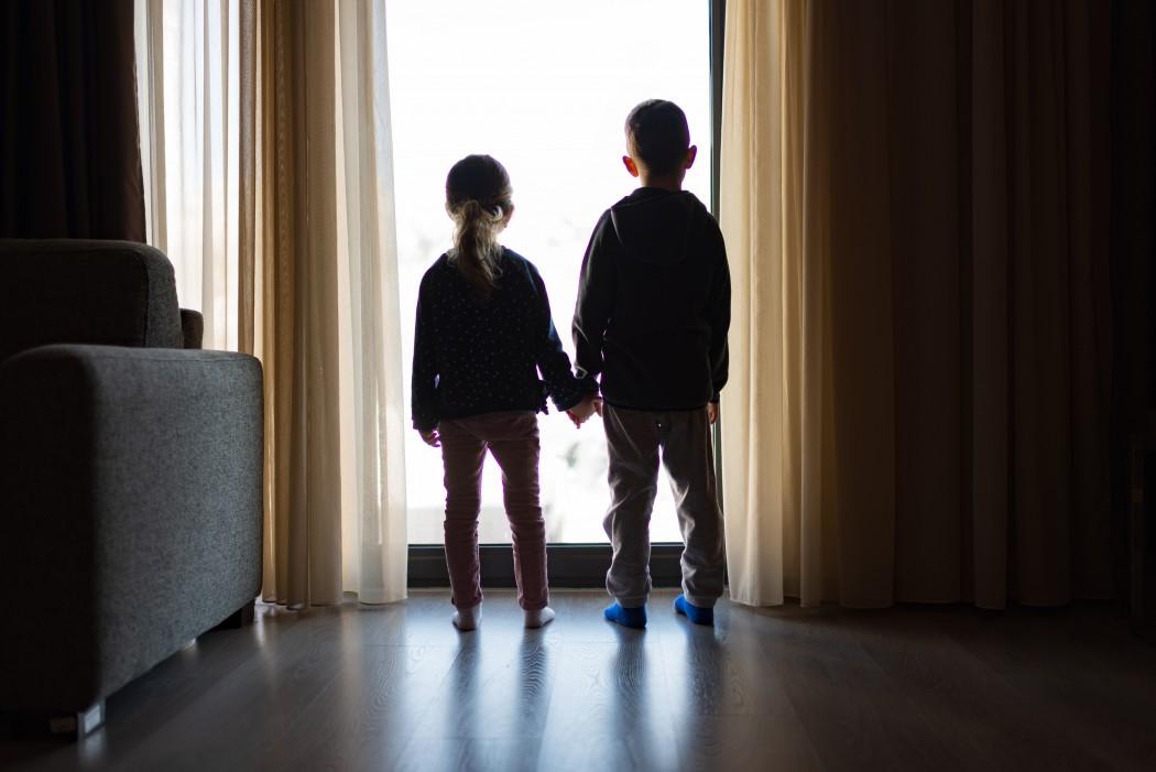 To barn som leier hverandre. De står foran et vindu med ryggen mot kamera. Det er mørkt i rommet.