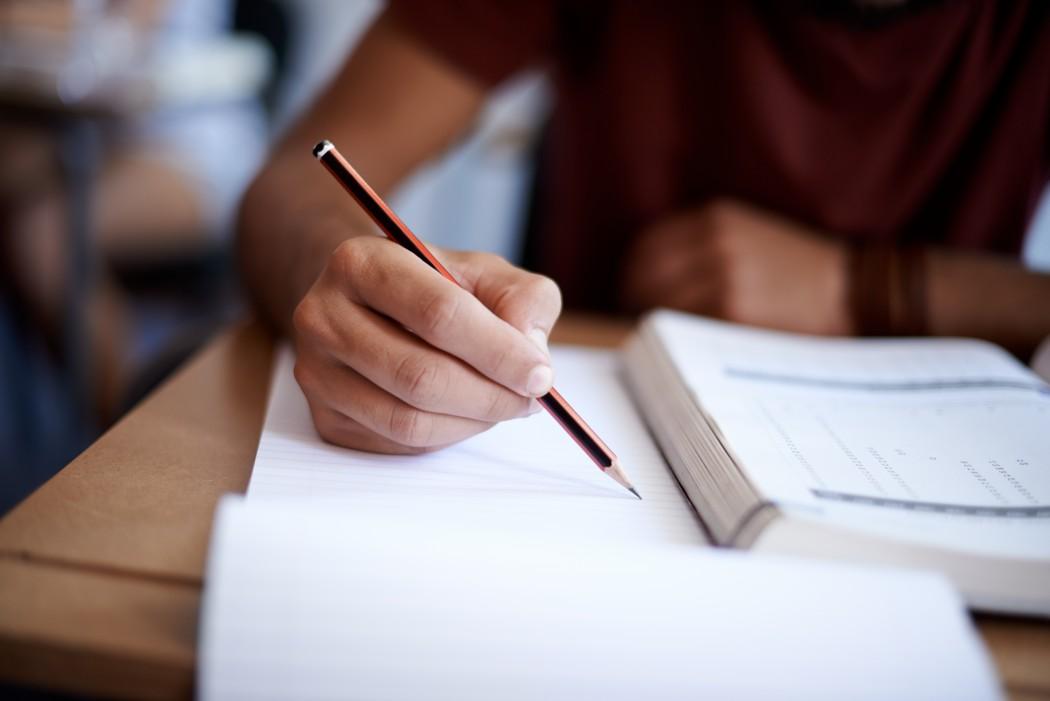 Hånd som noterer i skrivebok.
