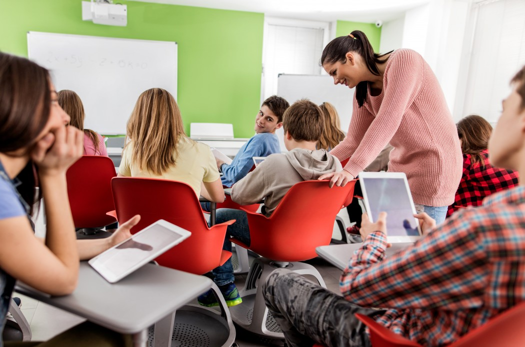 Klasseromssitausjon er lærer står ved siden av elev midt i klasserommet og snakker med ham. Elevene rundt følger med på samtalen.