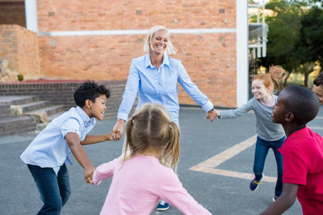 En voksen og fire barn holder hverandre i hendene i en sirkel. Alle smiler.