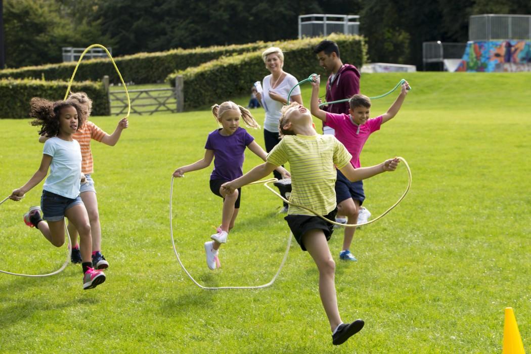 Fem barn hopper tau. To voksne følger med på leken.