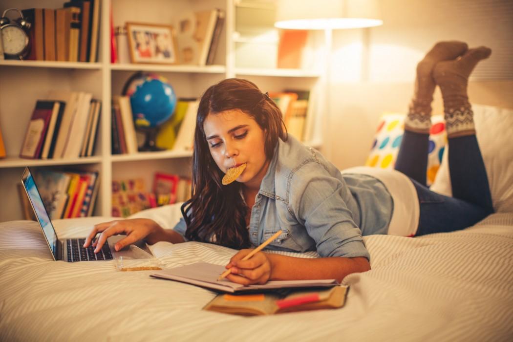 Jente som ligger på magen på senga med hånda på laptoppen mens hun skriver i en notatbok. Hun har en oppslått bok med postitlapper og en kjeks i munnen.