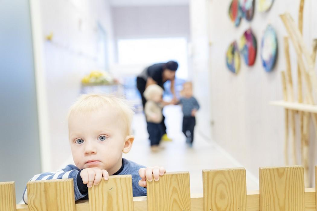 Liten gutt ser over en grind inne i barnehagen. I bakgrunnen skimtes en ansatt og to barn. Bakgrunnen er for uskarp til at man kan se hva de gjør.