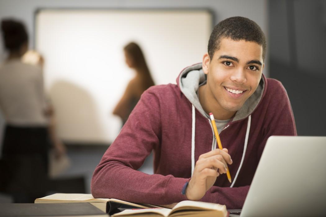Vgs-elev som ser rett i kamera og smiler. Sitter foran en skjerm, med en blyant i hånden og medelever i et klasserom i bakgrunnen.