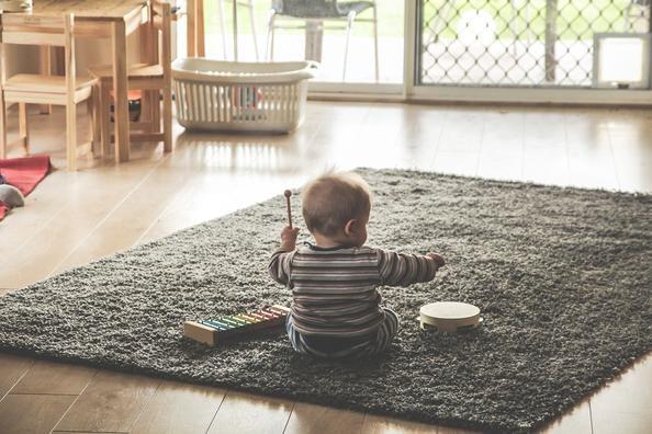 Baby som sitter alene på et gulvteppe med et par musikkinstrumenter innen rekkevidde.
