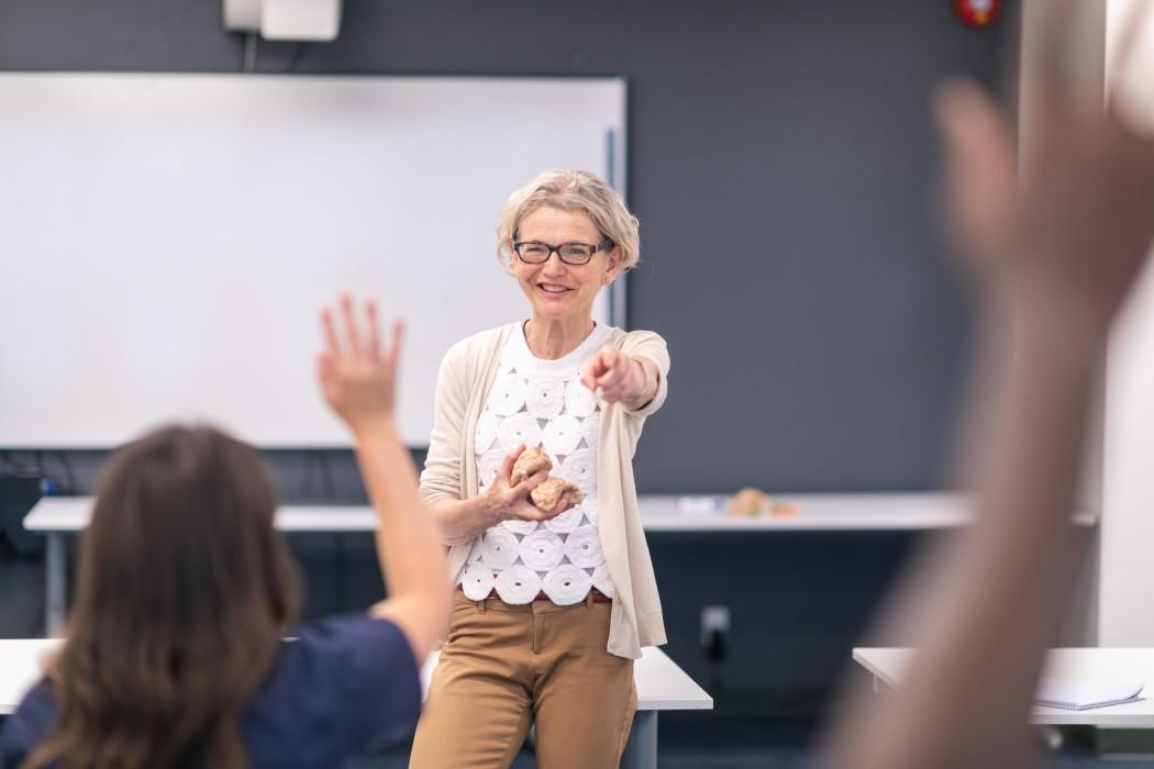 En smilende lærer som peker på en elev som rekker opp handa
