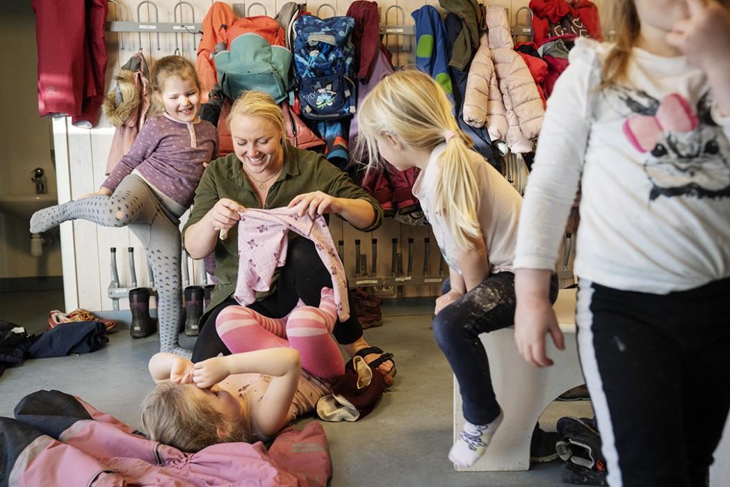 En barnehageansatt holder på å kle på et barn som ligger på ryggen foran henne. To andre barn ser på. Et barn er på vei ut av bildet. Stemningen er god.