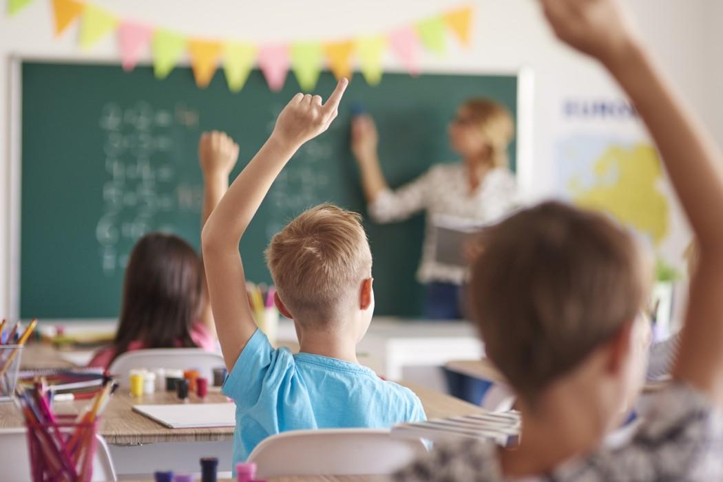 Elever som rekker opp hånda. I bakgrunnen skimtes en lærer som peker på noe på tavla