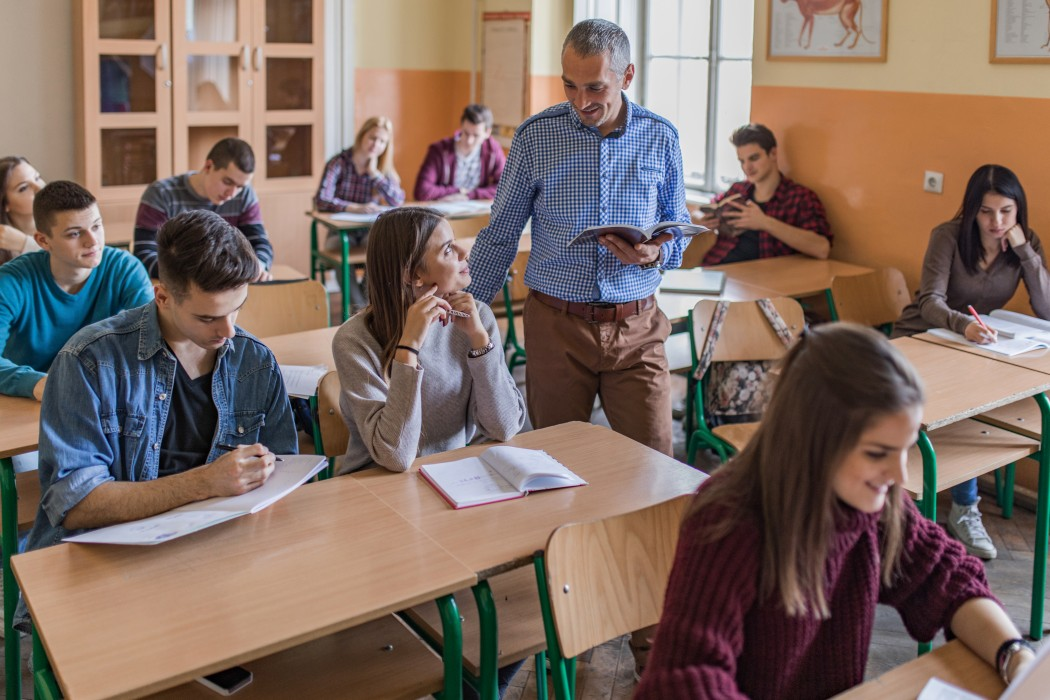 Lærer og elev ser på hverandre. Lærer står ved siden av elevens pult