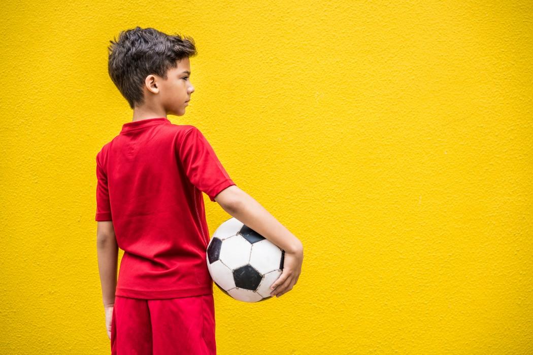 Gutt som står med ryggen til kamera, med en fotball under armen.