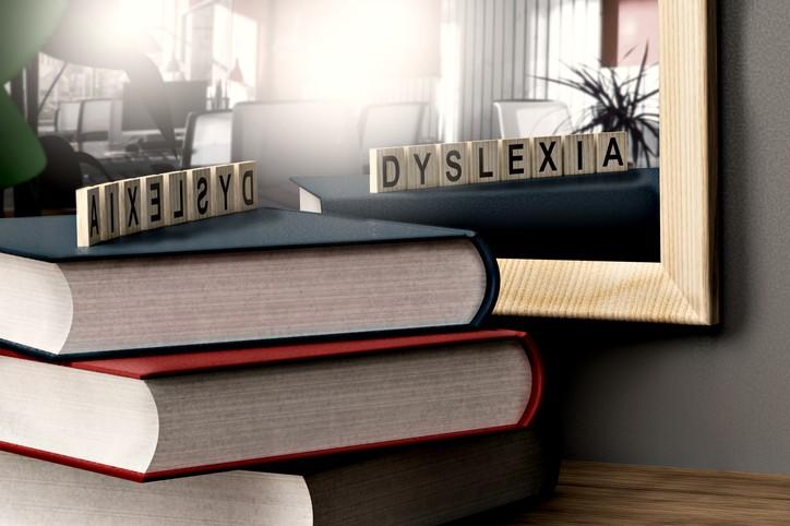 Bokstabel foran et speil, med bokstavbrikker som danner ordet dyslexia