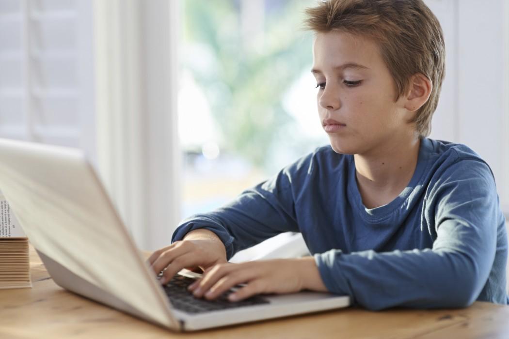 Gutt skriver på en bærbar PC