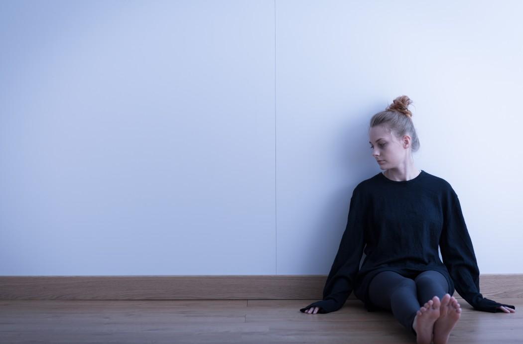 Ei jente sitter alene på gulvet med ryggen mot en vegg.