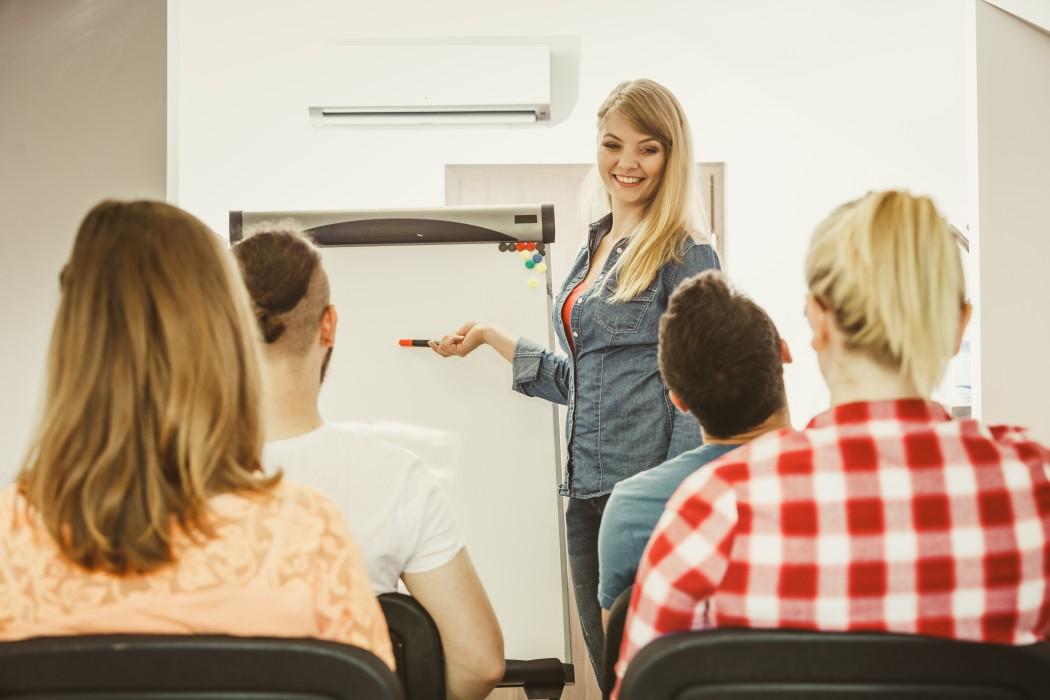Smilende lærer peker på tavla og ser utover klassen