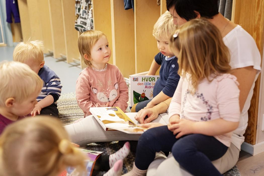 Barnehageansatt sitter i garderoben og leser bok for seks barn. Har god blikkontakt med et av barna. To andre barn sitter på fanget. De andre sitter rolig rundt henne i en sirkel.
