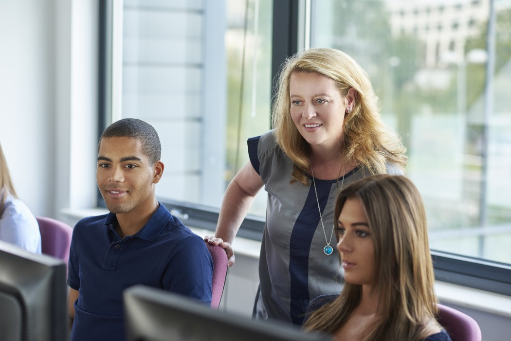 Smilende lærer ser over skulderen til to avslappede elever som sitter ved en pc
