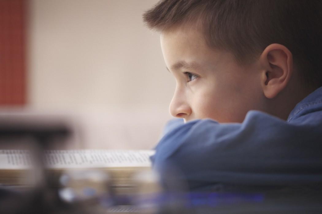 Gutt sitter med haka på hendene/bordkanten og stirrer tomt framfor seg