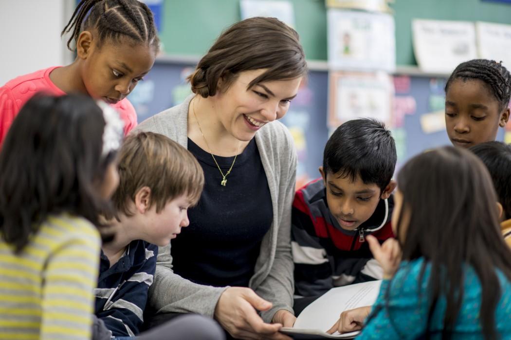 Blid lærer omgitt av elever mens hun viser dem noe i en bok